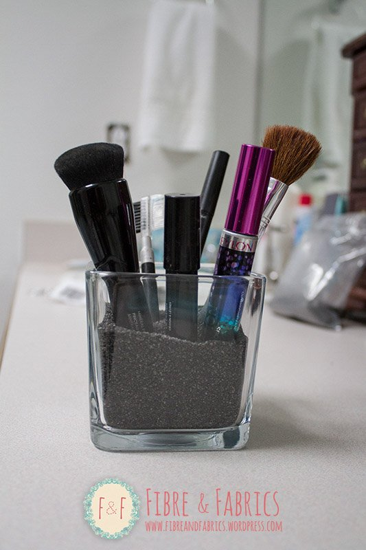 Dollar Tree bathroom organization - glass container with black rice and vertical make up items standing inside