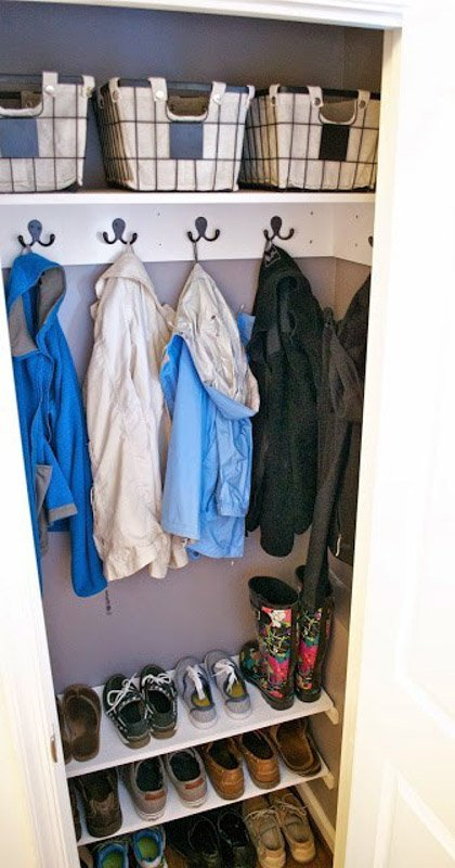 narrow coat closet with hooks mounted on the wall to hold jackets