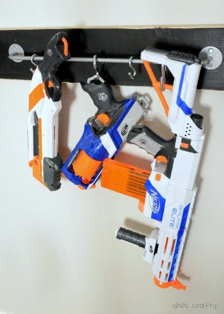 Three nerf guns hanging on s-hooks hooked to a metal rod on the wall.