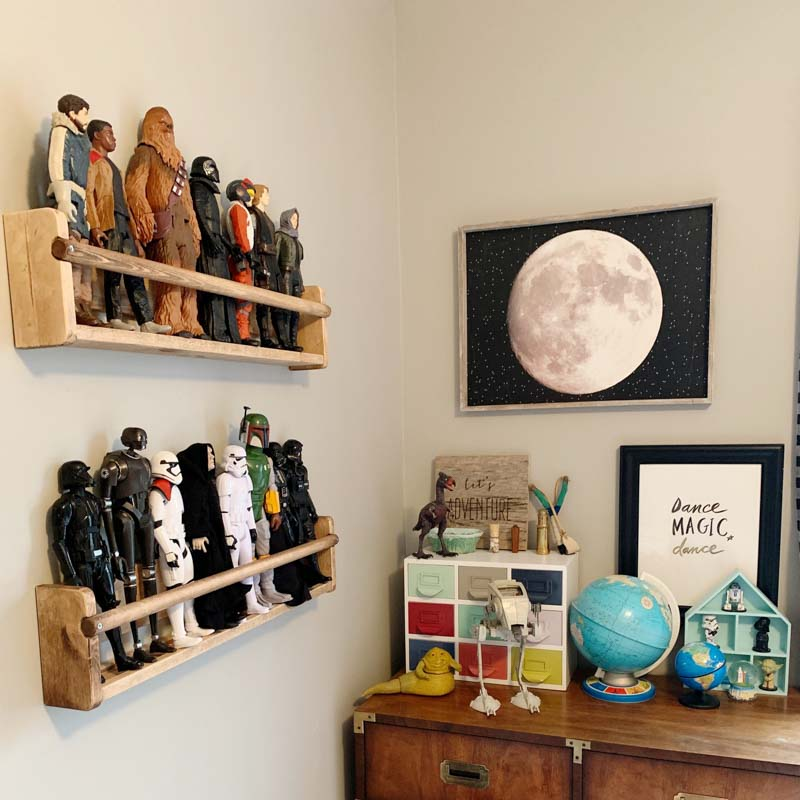 Small wooden bookshelves displaying action figures - all from Star Wars.