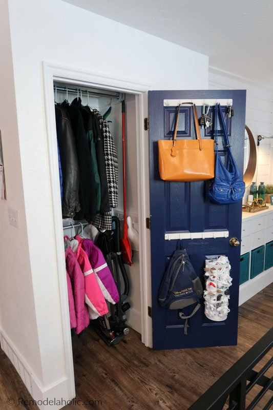 An open coat closet with jackets hanging on an extra rod added to the lower section of the closet.