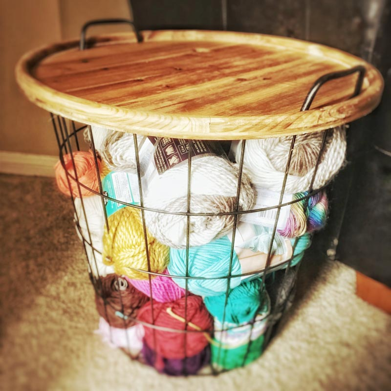 wire basket with filled with yarn balls and a wooden table top on top.