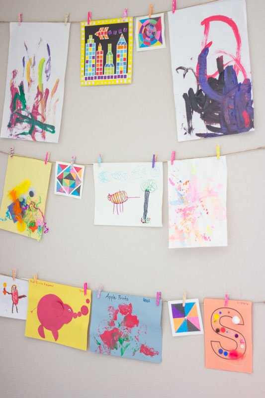 A line of twine with clothespins displaying children's art work.