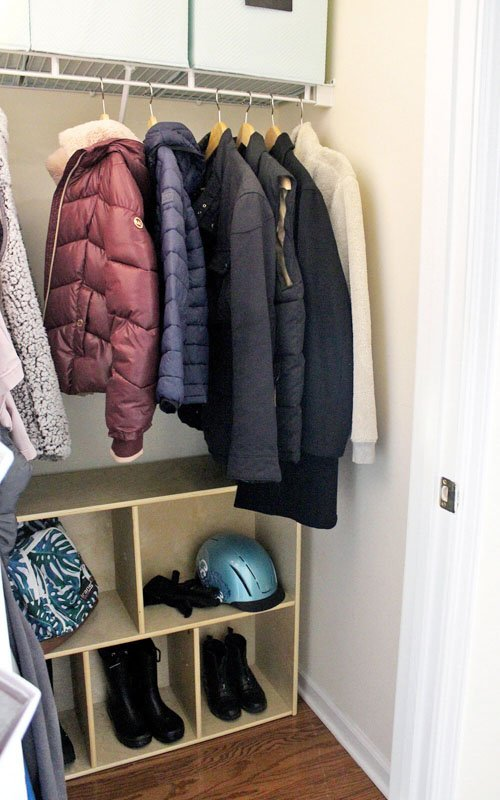 A cube storage shelf at the base of a closet for extra storage.