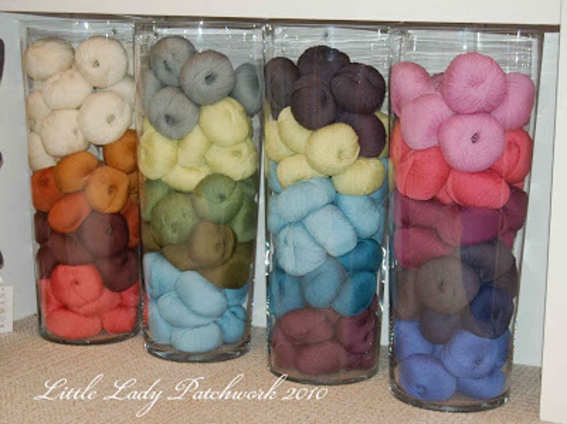 yarn stacked in 4 clear tall vases
