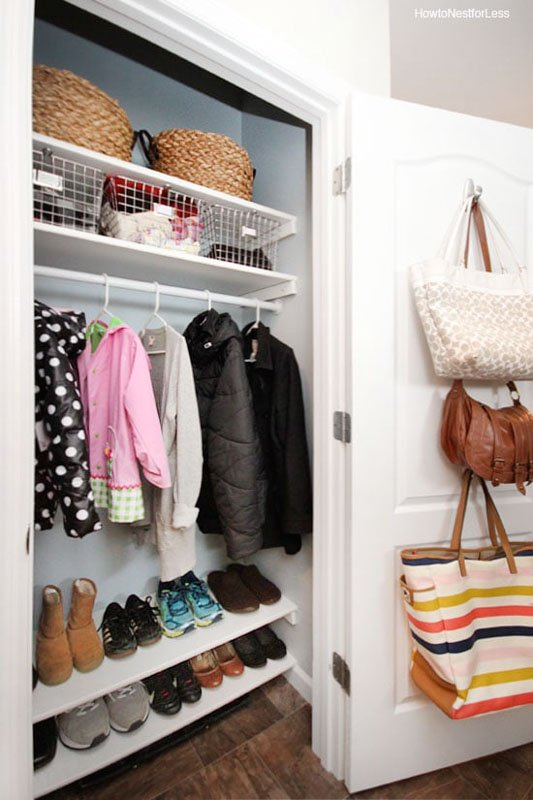organized coat closet with built in shoe shelving, hanging jackets and hanging purses