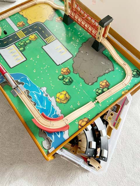 A train table for play with a storage bin underneath filled with accessories.