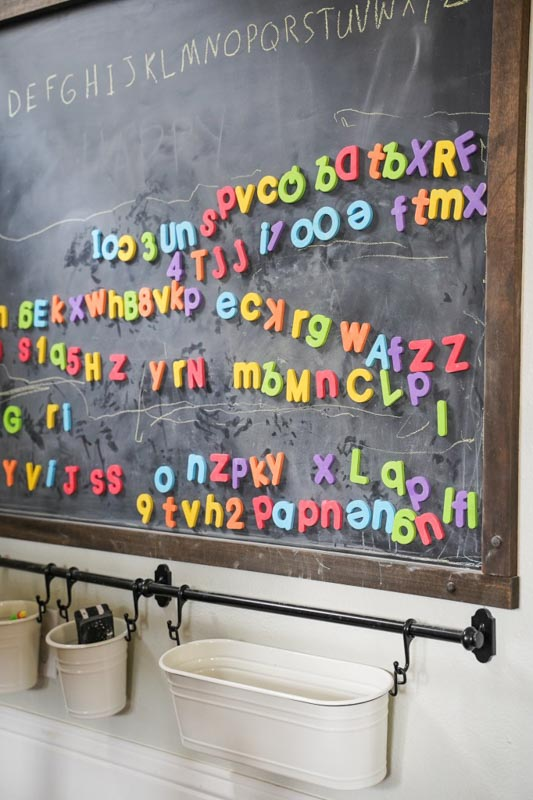A chalkboard covered in ABC magnets and hanging baskets below for storage.