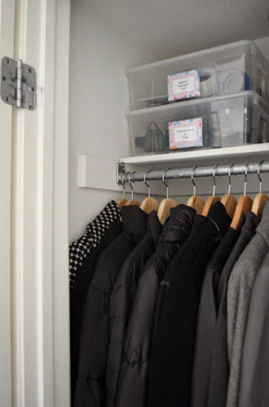 Clear, plastic bins stacked on a top shelf of a closet for coats.