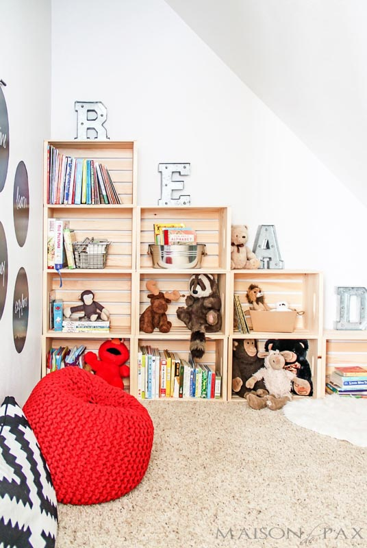 Stacked wooden crates in a playroom for book and toy organization.