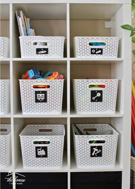 White plastic bins on cube shelving with labels on each featuring a picture in place of words.