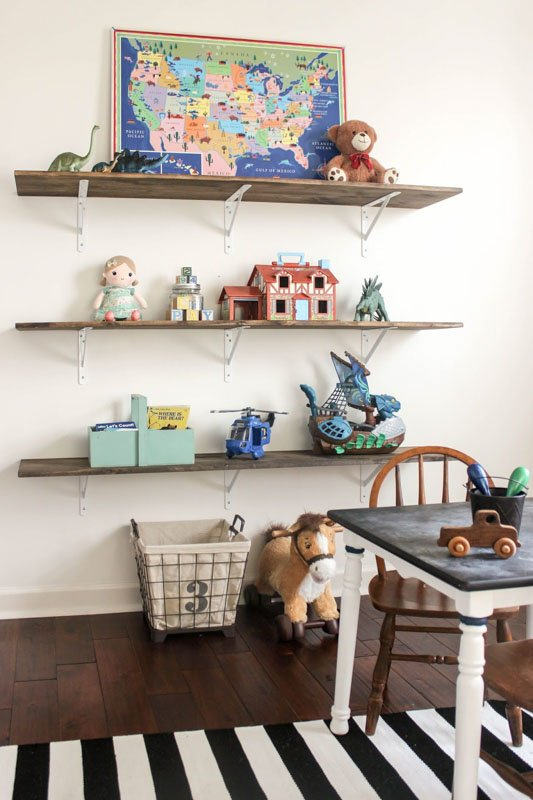 DIY open shelving on a playroom wall, lined with dinosaurs, play sets, blocks and more.