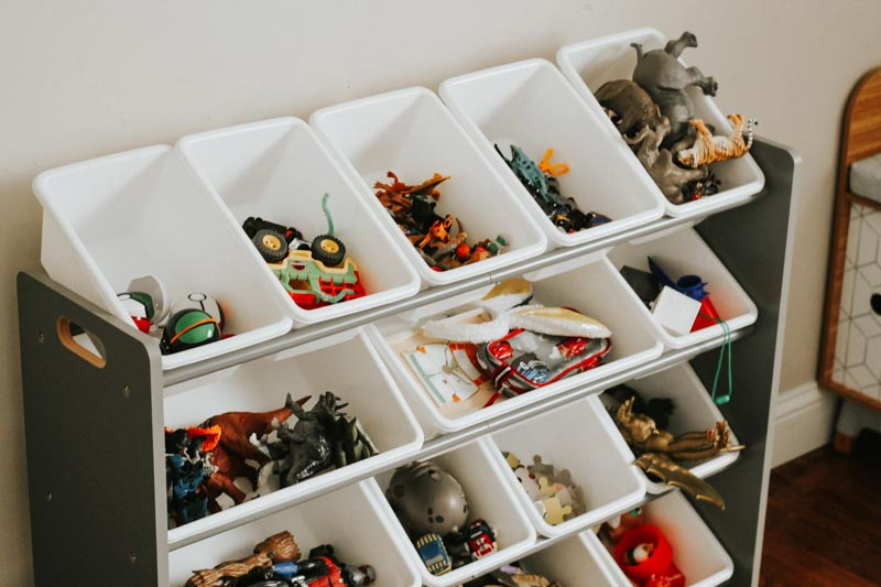 A toy organizer filled with small and large white plastic bins.