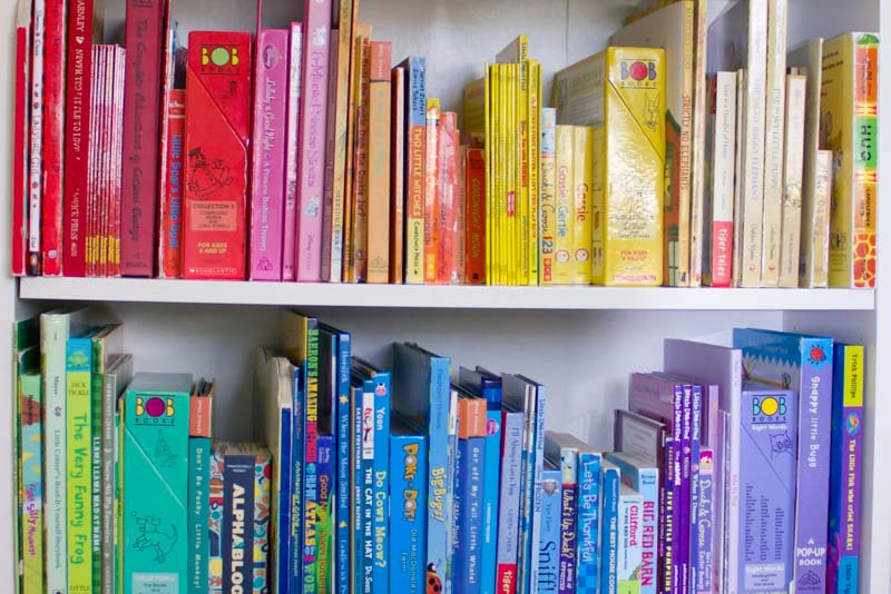 Children's books on a white bookshelf grouped together by color.