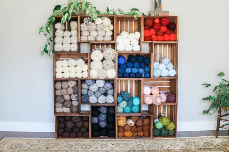 wall of crates with yarn sorted by colors in them