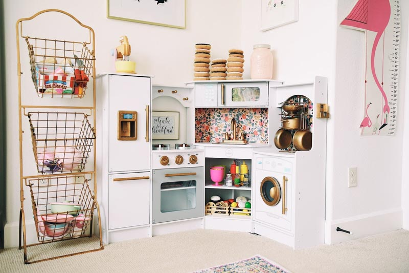 Play kitchen with wire tiered shelves for pretend food storage.