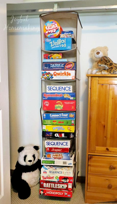 Board games stored in a hanging closet organizer.