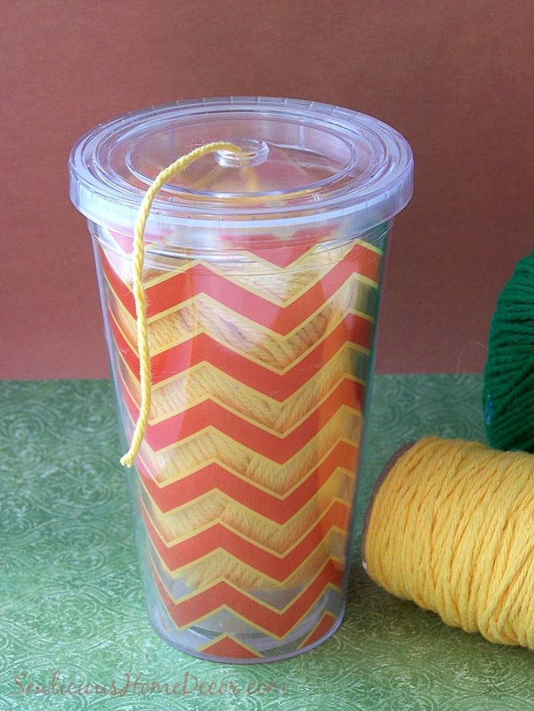 Yarn inside a see through plastic cup with end coming out of cap to keep tidy