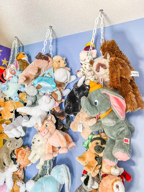 Stuffed animals hanging from white, plastic chains with clips.