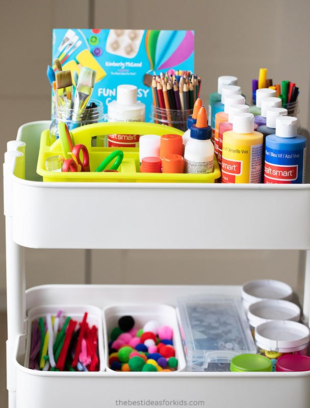White rolling cart storing paint and other craft supplies for playroom organization.