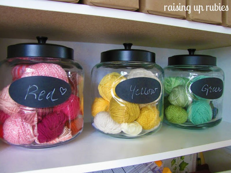 glass jars filled with yarn separated by color