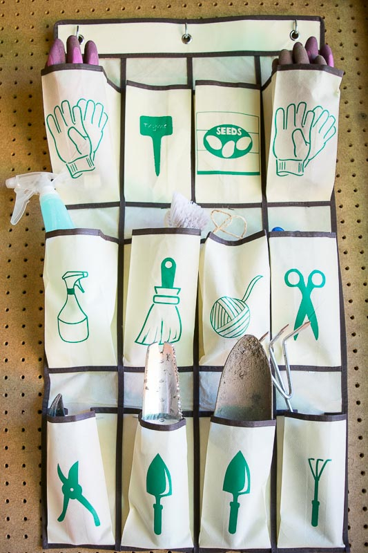 A hanging shoe organizer with labeled pockets for garden tool shed organization.