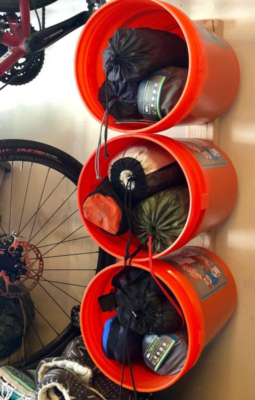 Large, orange paint buckets mounted sideways to a shed wall, holding foldable chairs and sleeping bags.