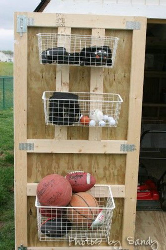 A shed door with white wire baskets mounted inside, filled with sports equipment.