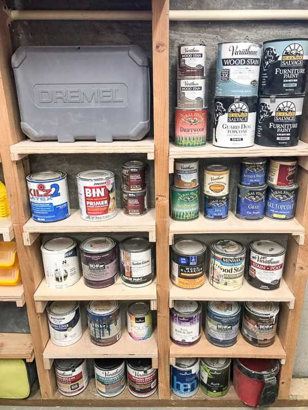Small pieces of wood mounted between the studs of an outdoor shed for extra storage space. The shelves are filled with small cans of paint.