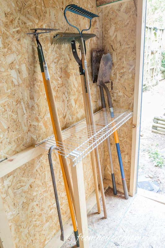 A metal wire shelf affixed to a shed wall for storing long yard tools.