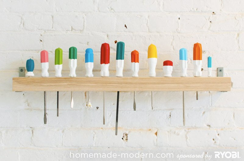 Screwdrivers with painted handles lined up in a wooden wall-mounted organizer.