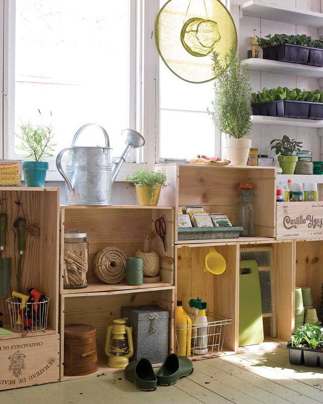 A collection of stacked wooden crates below a brightly lit window filled with gardening tools, supplies and potted plants.