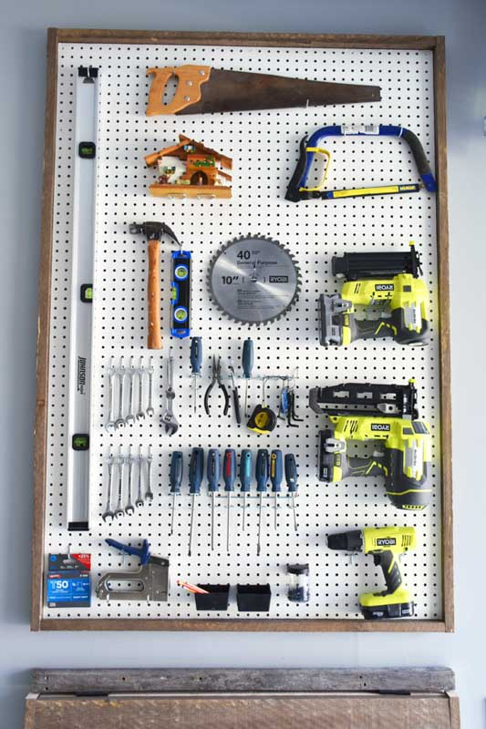 A framed sheet of pegboard storing power tools, accessories and other small tools in a shed.