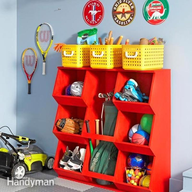 A red, wooden organizer DIY storing sports equipment, topped with three yellow baskets of gardening tools.