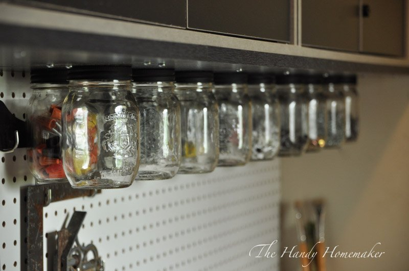 Mounted storage beneath a shed cabinet using mason jars with lids.