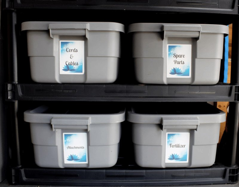 Large labeled storage bins for shed organization. Each bin is uniform in size and color.