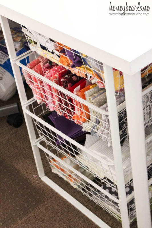 A white, wire basket cart with four drawers storing fabric.
