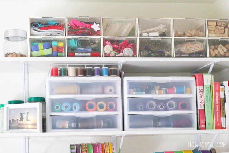 Various sizes of clear drawers displayed on a shelf in a sewing room for supply organization.