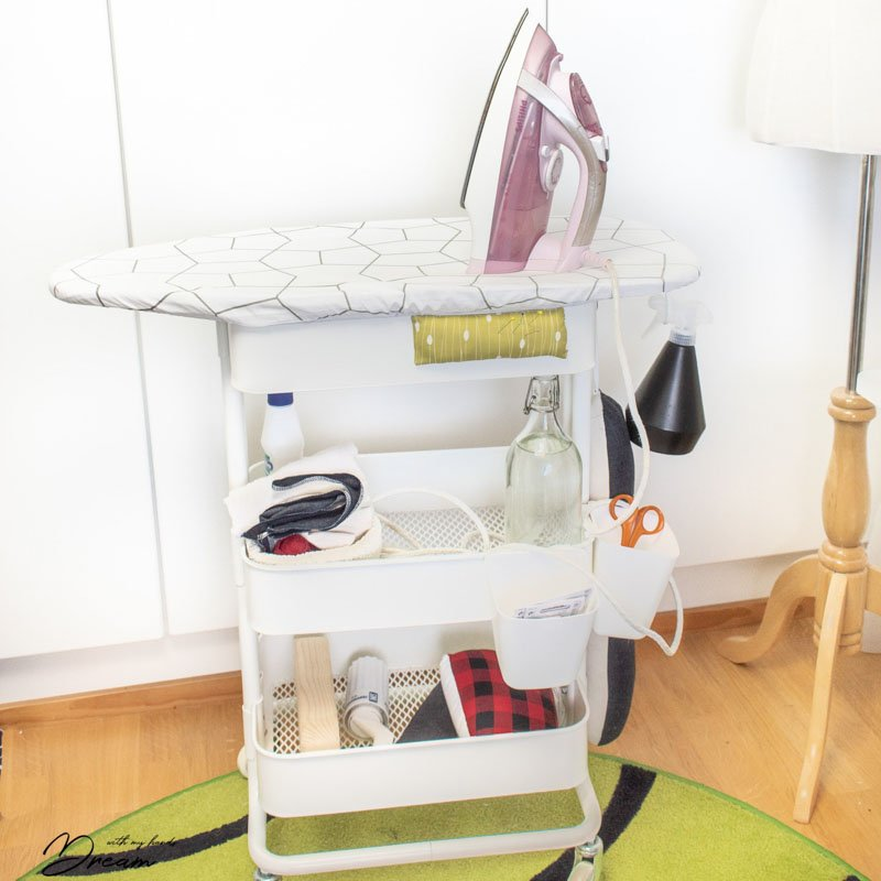 A three tiered cart fitted with a mini ironing board on top for easy and convenient ironing and sewing room organization.