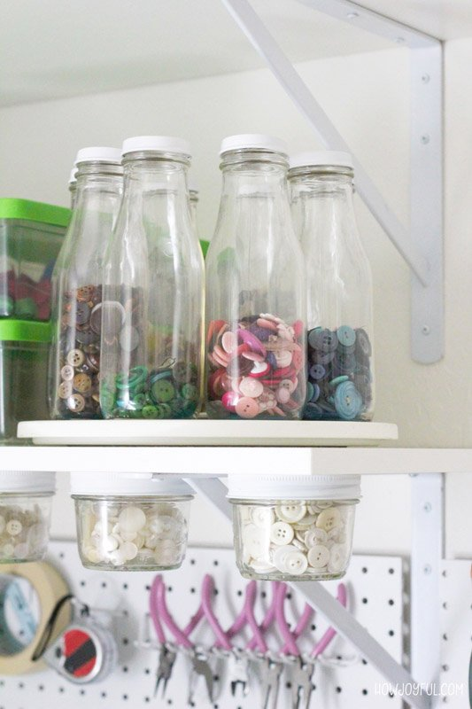Glass milk jugs used for button storage, sitting on top of a lazy susan.
