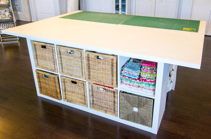 A cube shelf base for storage with a white tabletop as perfect sewing table, with cutting mats on the surface.