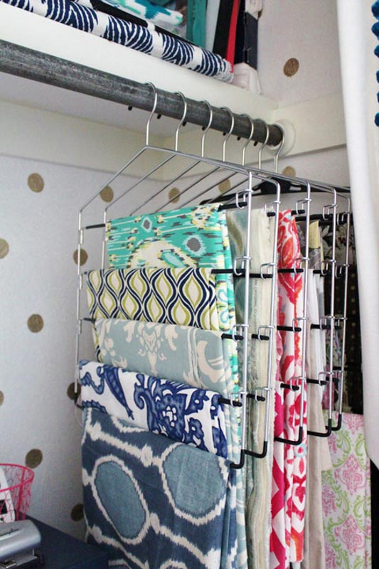 Specialty hangers meant for pants hanging on a closet rod, with fabric draped over each bar for sewing room organization.
