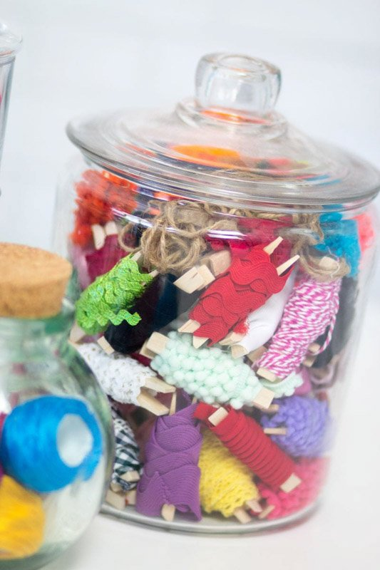 A glass jar with a lid full of sewing trim on clothespins.