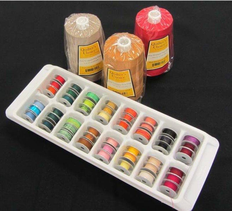 Bobbins of assorted threads stored in a dollar store ice cube tray for sewing room organization.