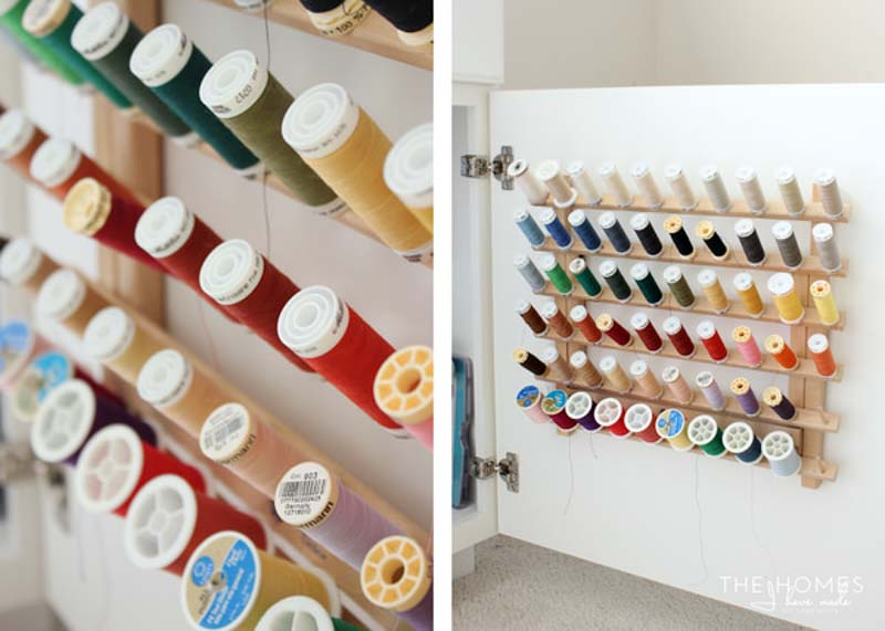 Spools of thread on a wooden organizer, mounted inside of a cabinet door.