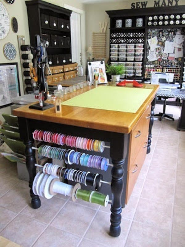 Multicolored ribbon spools on tension rods hung between legs of a sewing table.