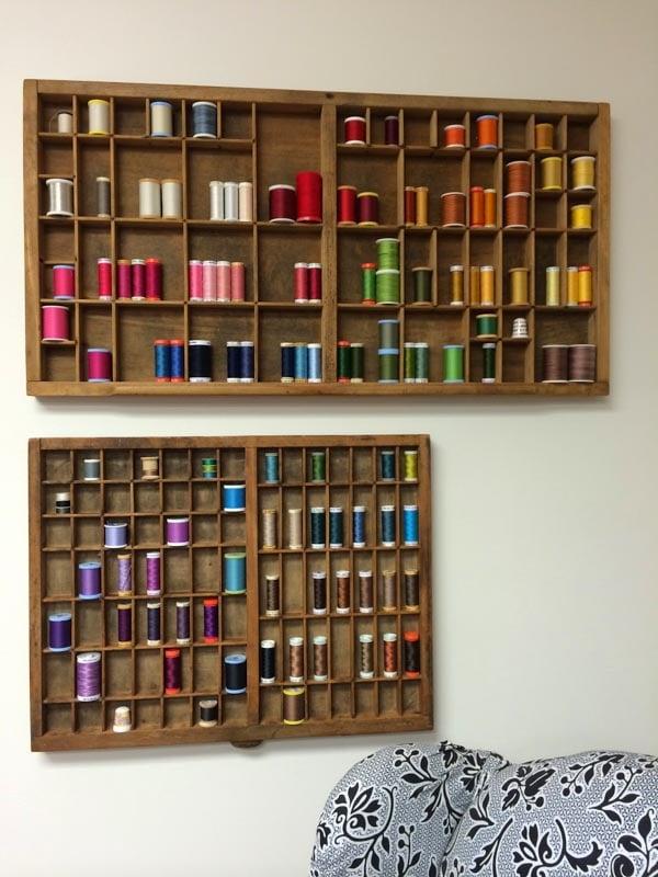 Thread organized in antique printer's trays on a wall in a rainbow fashion.