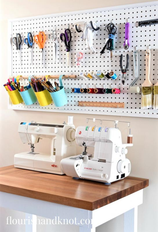 A peg board mounted on the wall above a sewing table for sewing room tool organization.