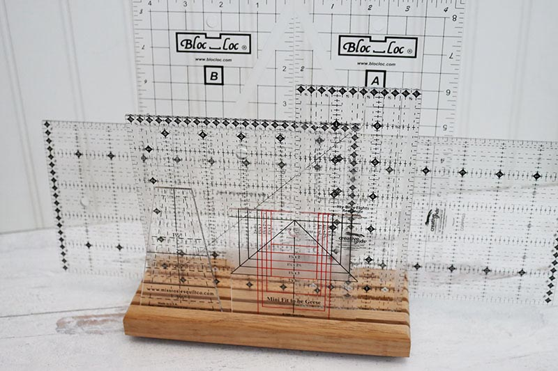 A wooden stand with long grooves in it holding a selection of plastic sewing rulers.