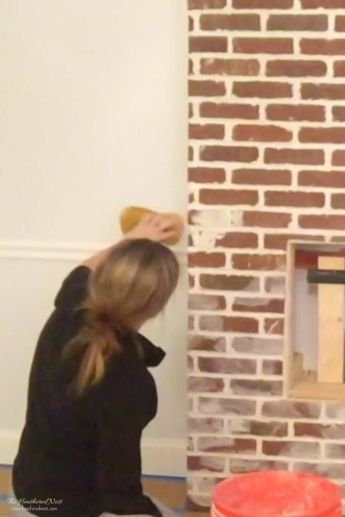 woman performing the german smear on a brick fireplace